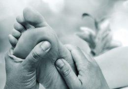 Macro close up of Reflexologist doing massage on female foot.